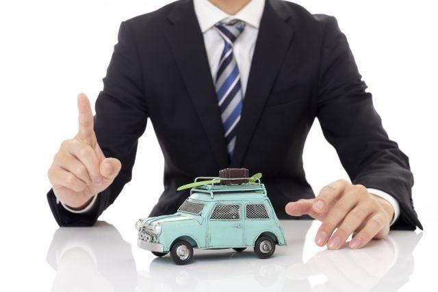 机に置かれたミニチュアの車とビジネスマン