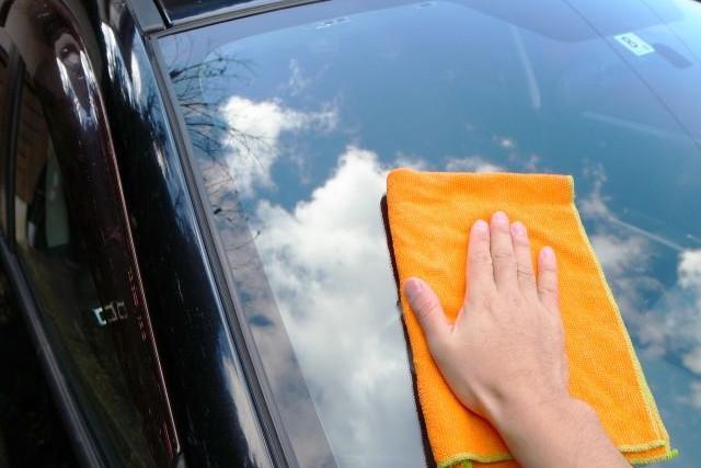車のフロントガラスを拭く人